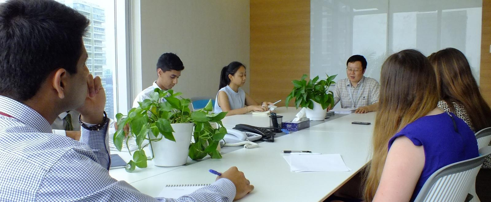 Students doing internships in Asia participate in a meeting with business professionals in China.